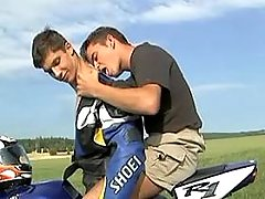 Young smooth gay bikers enjoy oral love in nature